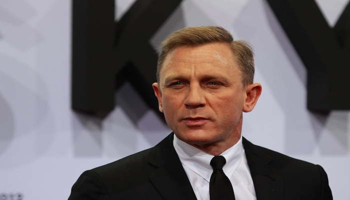 Daniel Craig dressed in a black suit and tie.