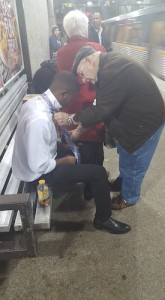 An elderly gentleman teaches a young man how to tie his tie