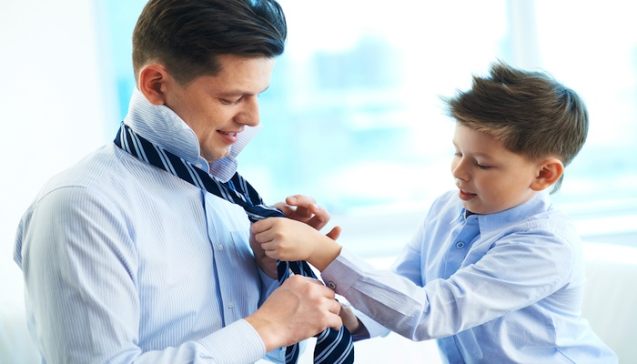 A young boy helps his Dad tie his tie
