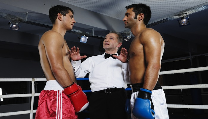 Boxing referee wearing a bow tie while separating boxers