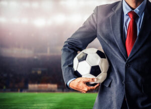 soccer manager holding football